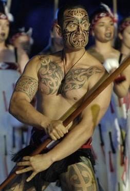 un guerriero maori con tatuaggi a fascia sulle braccia e le gambe